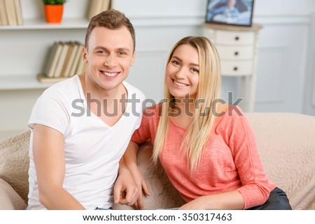 Happy pair. Young couple looks happy while sitting on the sofa and smiling merrily - stock photo