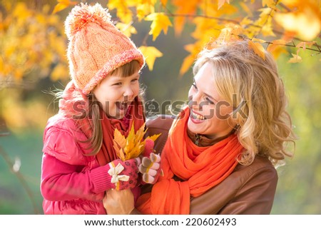 Happy parent and kid holding autumn yellow leaves outdoor. - stock photo