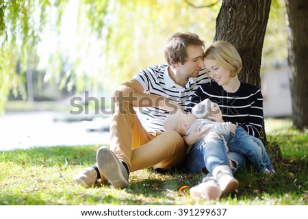 Happy parenthood: young parents with their sweet baby girl in sunny park  - stock photo
