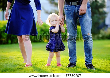 Happy parenthood: young parents with their sweet toddler girl in sunny park. The whole family dressed in the same color scheme. Family style clothing. - stock photo