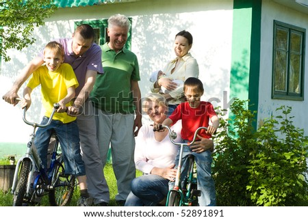 happy parents and children play together outdoors - stock photo