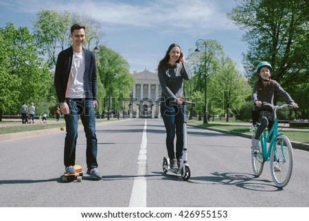 Happy Parents and Children Ride a Bike, Skateboard and Scooter Together in City - stock photo