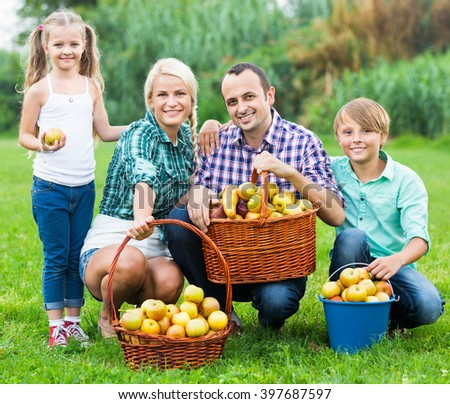 Happy parents and children with baskets of ripe apples outdoors - stock photo
