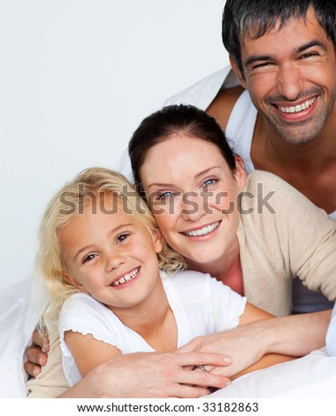 Happy parents and daughter on bed smiling at the camera - stock photo