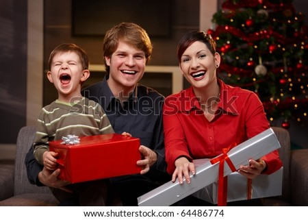 Happy parents and son sitting at couch, holding christmas gifts, laughing.? - stock photo