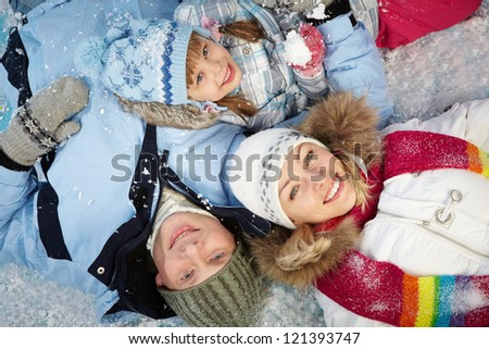 Happy parents and their daughter in winterwear lying in snow - stock photo