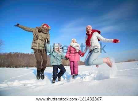 Happy parents and their kids having fun outside in winter - stock photo