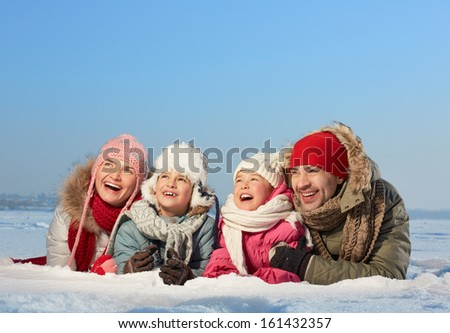 Happy parents and their kids in winterwear lying in snow - stock photo