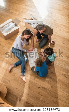 Happy parents are sitting barefoot on the floor of their new house They are looking at the house model with their daughter and son They are surrounded by open cardboard boxes and palette for the paint - stock photo