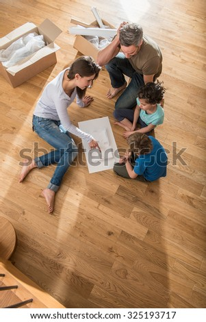 Happy parents are sitting barefoot on the floor of their new house. They are showing their room to their daughter and son on the house model. They are surrounded by open cardboard boxes - stock photo
