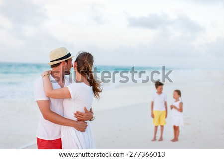 Happy parents at tropical beach with two kids standing on background - stock photo