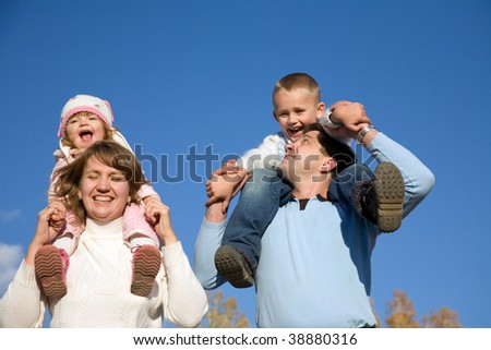 Happy parents hold on shoulders of beautiful small children against the blue sky - stock photo