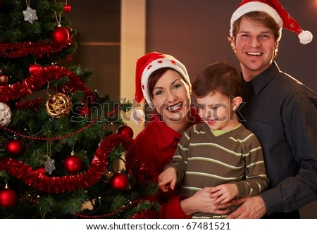 Happy parents holding small child at christmas tree, boy pointing at tree. - stock photo