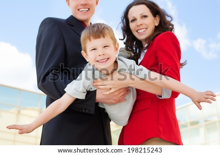 Happy  parents holding their son showing plane outdoor on a summer day - stock photo