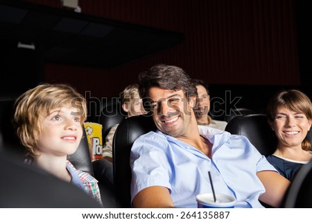 Happy parents looking at son watching movie in cinema theater - stock photo