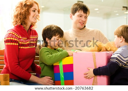 Happy parents looking at their children while they trying to unwrap gifts - stock photo