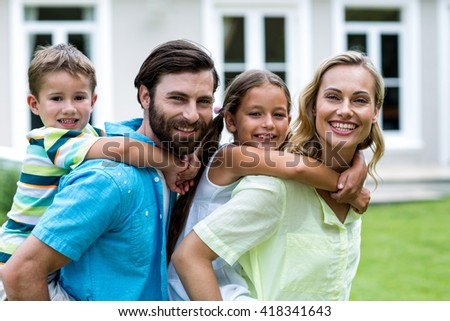 Happy parents piggybacking children outside house in yard - stock photo
