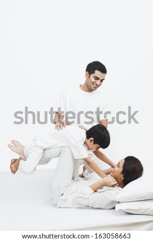 Happy parents playing with their son on the bed - stock photo