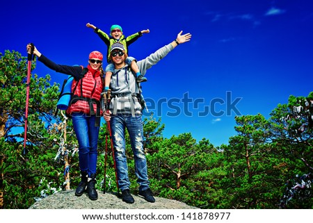 Happy parents standing on the peak of a mountain with their little son. - stock photo