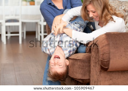 Happy parents tickling son and fun laugh - stock photo