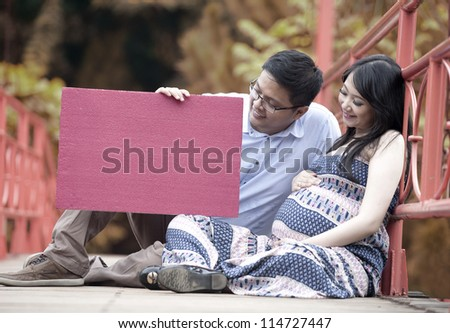 Happy parents to be holding a blank board/copy space - stock photo