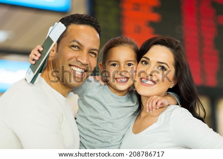 happy parents travelling with their daughter at airport - stock photo