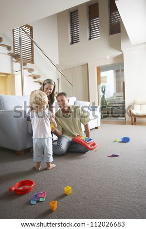 Happy parents watching daughter playing with toy at home - stock photo