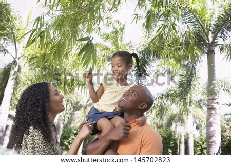 Happy parents with daughter enjoying together in park - stock photo