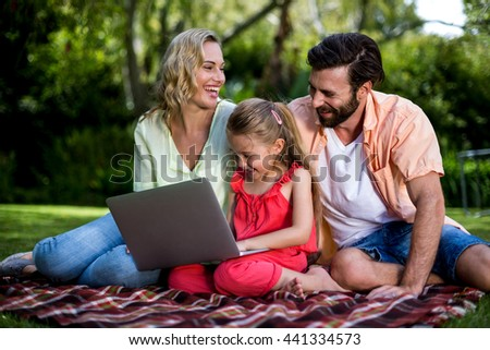 Happy parents with daughter using laptop while sitting at yard - stock photo