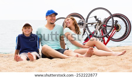 Happy parents with kid having rest after cycling on the beach - stock photo