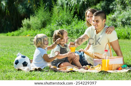 Happy parents with little girls having picnic at countryside  - stock photo