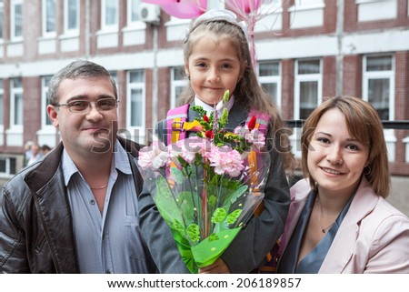 Happy parents with schoolgirl standing on campus - stock photo