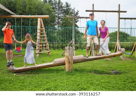 Happy parents with son and daughter jumping on a swing on a wooden playground - stock photo