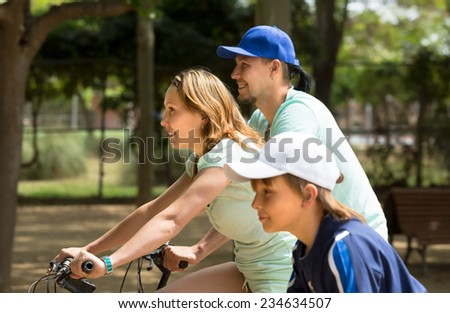 Happy parents with teenager son cycling through city in summer day - stock photo