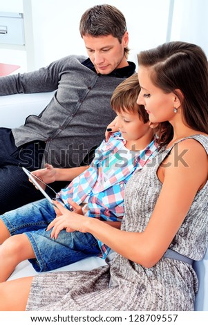 Happy parents with their son looking at touchpad pc together at home. - stock photo