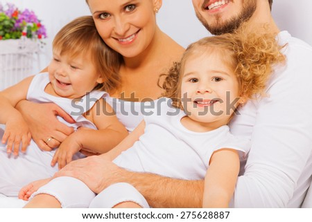 Happy parents with two adorable children lay on bed in white pajamas together in the morning - stock photo