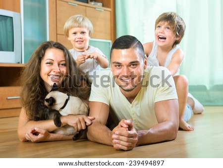 Happy parents with two daughters and a cat in the house - stock photo
