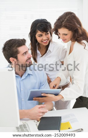 Happy partners using digital tablet together in the office - stock photo