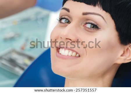Happy patient at the dentist's office. Dentist makes the process of treatment of a beautiful young girl. - stock photo