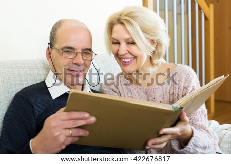 Happy pensioners watching old photoes in family album at home - stock photo