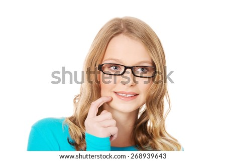 Happy pensive teenage woman with finger on cheek - stock photo