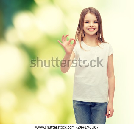 happy people and gesture concept - smiling little girl in blank white t-shirt showing ok gesture - stock photo