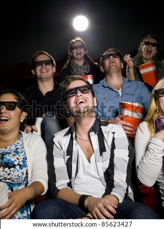 Happy people at the movie theater wearing 3d glasses - stock photo