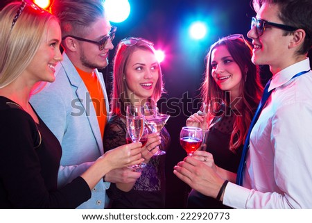 Happy people clinking by glasses with each other - stock photo