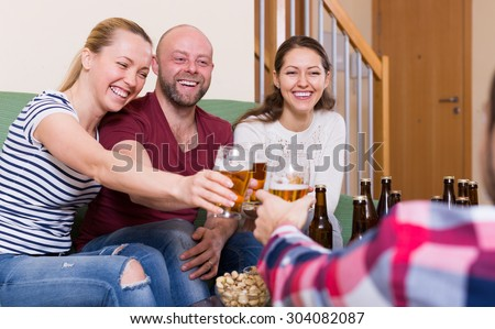 Happy people drinking beer  and laughing at home - stock photo