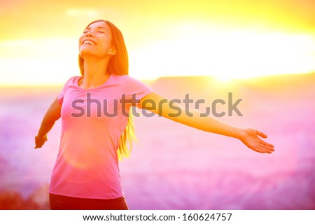 Happy people - free woman enjoying nature sunset. Freedom and serenity concept with female model in ecstatic enjoyment. Mixed race Asian Caucasian female model in 20 enjoying sunset, Grand Canyon, USA - stock photo