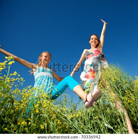 Happy people jumping in field - stock photo