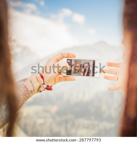 Happy people make selfie on mobile phone at mountain outdoor. Concept of friendship couple at blue sky background - stock photo