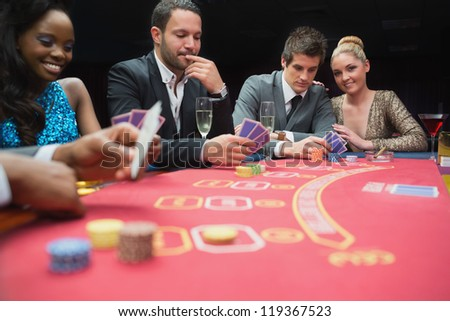 Happy people playing poker in casino - stock photo