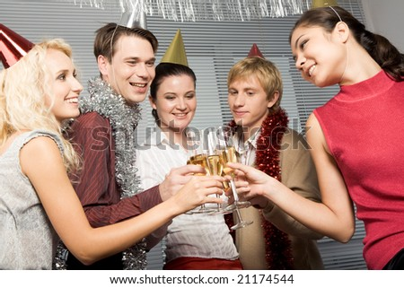 Happy people toasting with glasses of champagne in hands while looking at each other joyfully - stock photo